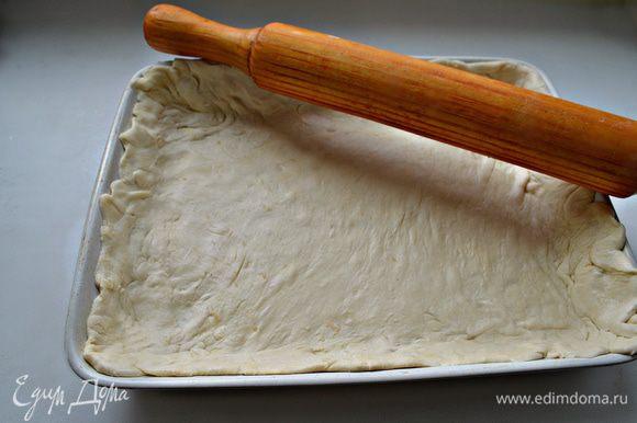 """Тесто разморозить. Раскатать на слегка присыпанной мукой поверхности по размеру формы, оставляя немного теста на """"бортики"""". Форму для выпечки смазать растительным маслом. Уложить тесто."""