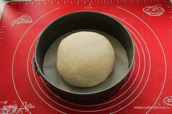 Придаем тесту круглую форму и перекладываем его в форму, смазанную растительным маслом или застеленную бумагой для выпечки. Накрываем полотенцем и оставляем на 30-50 минут в теплом месте.