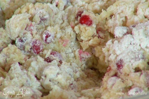 Влить яично-молочную смесь в муку с ягодами и вымешать тесто.