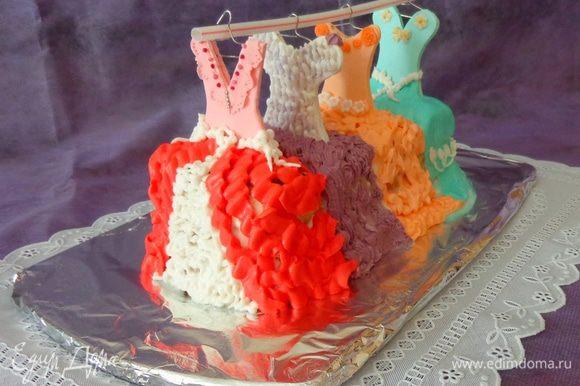 Воткнуть палочки с верхними частями платьев в торт и с помощью разноцветного крема (тот, который белковый) нарисовать низ платьев. Из подручных материалов (у меня трубочка для коктейля) сделать основу для вешалки.