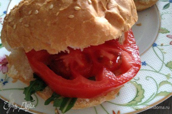 Булочки разрезать, положить ч/л сливочного соуса или майонеза, руколу, дольку помидора (у меня очень большой помидор).