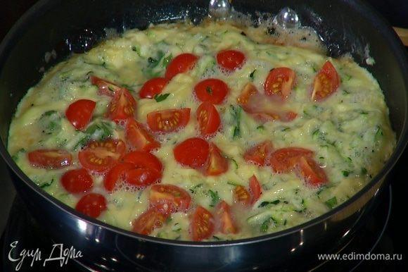 Посыпать омлет оставшимся российским сыром, выложить порезанные помидоры, накрыть сковороду крышкой и готовить еще 2–3 минуты.
