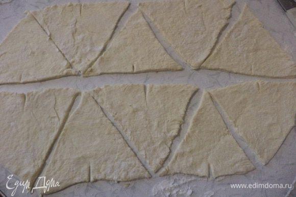Размороженное тесто раскатать в прямоугольный пласт, разрезать на треугольники среднего размера.