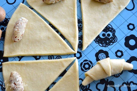 Из каждого кусочка марципановой начинки скатайте маленькую колбаску и выложите на тесто с более широкого конца. Сверните рогалик, наподобие круассана. Таким же образом приготовьте все остальные рогалики.