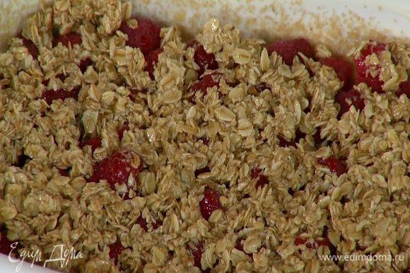 На дно формы выложить малину (немного ягод оставить), полить виски и оставшимся медом и присыпать овсяными хлопьями с маслом.