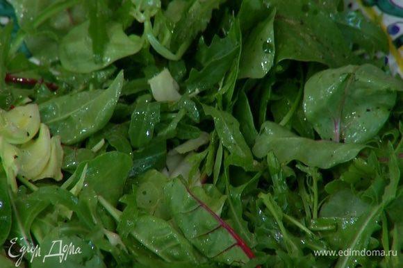 На большое блюдо выложить салатные листья, сбрызнуть оливковым маслом, полить оставшимся лимонным соком, посолить, поперчить и перемешать.