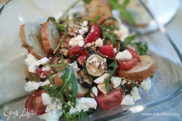 В салатницу выложить руколу, овощи, четвертинки помидоров. Полить заправкой. Раскрошить фету и сдобрить гренками. Остальные гренки подать дополнительно.