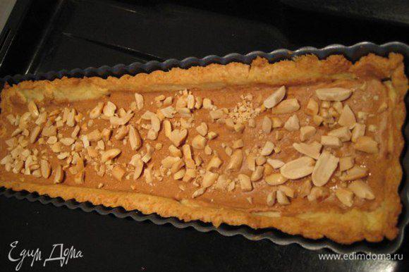 По дну горячего тарта распределить арахисовое масло, посыпать рубленым жареным арахисом.