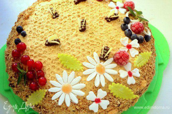 Снять пленку с верха торта и украсить цветочками из мастики, ягодами и шоколадными пчелками.