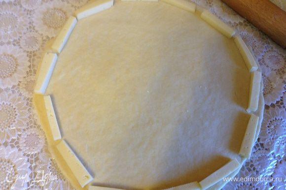 Раскатать тесто в круг, по краю выложить остаток сыра нарезанный брусочками.