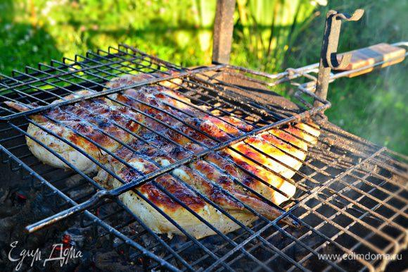 Выложите курицу на решетку, поместите над горячими углями и быстро обжарьте до румяной корочки с обеих сторон. Затем раздвиньте угли в разные стороны и поместите решетку между ними. Доведите курицу до готовности (около 20 минут), периодически переворачивая.
