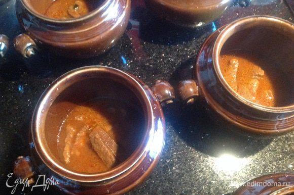 В подготовленные горшочки сначала выложите мясо вместе с соусом...