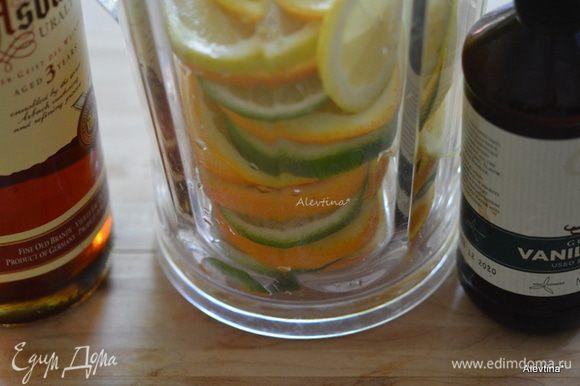 Заполнить кувшин цитрусами, залить белым вином, бренди, ванильным экстрактом. Поставить в холодильник на 2 часа.