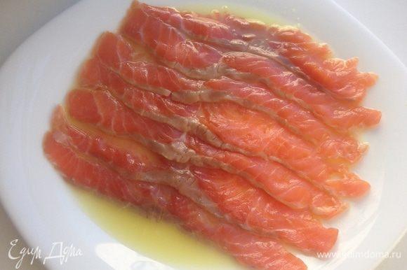 Нарезать форель тонкими слойками и разложить по тарелке с соком в один слой.