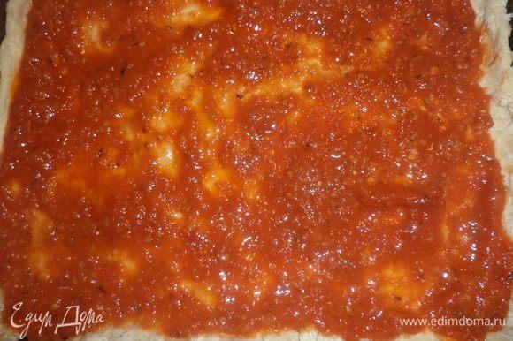 Противень смазать оливковым маслом. Тесто тонко раскатать, выложить тесто на противень, покрыть тесто соусом.