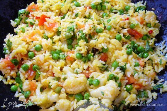 Рис отправить в вок, следом добавить помидоры, цветную капусту, зеленый горошек, петрушку. Немного посолить, прогреть 5 мин.