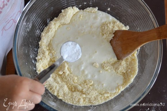 А в миску с оставшейся сухой смесью добавить кефир, соду. Перемешать.