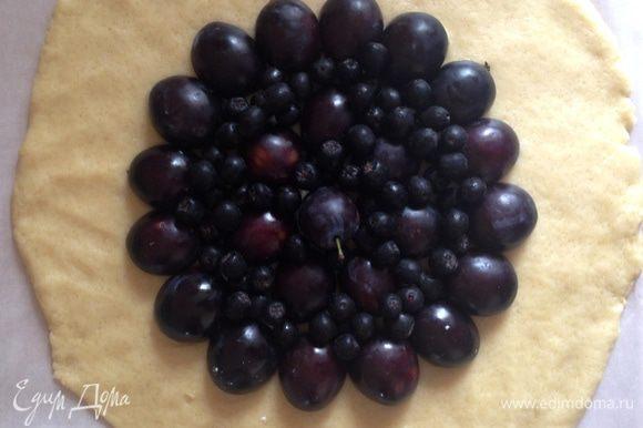 Тесто выложить на лист пергамента и раскатать в лепешку 30-33 см. Сверху выложить половинки слив и ягоды рябины.