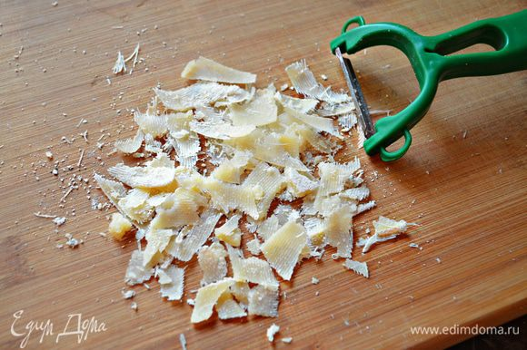 Пармезан (или любой другой твёрдый сыр) натрите на крупной тёрке или с помощью овощечистки и за 3 мин до готовности посыпьте пирог сыром.