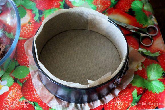 Заранее подготовьте форму со съемными бортами d=18 см. Выложите полученную крошку в форму, проложенную пергаментной бумагой. Разровняйте.