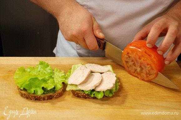 На сэндвич выложить листья салата, нарезанный огурец, куриное филе, а затем ломтики помидора.