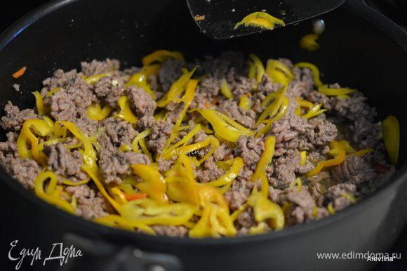 Разогреть духовку до 190C. Обжарить слегка говяжий фарш нежирный на разогретой сковороде. Добавить нарезанный цветной перец. Обжаривать еще 5 мин. Слить жир.
