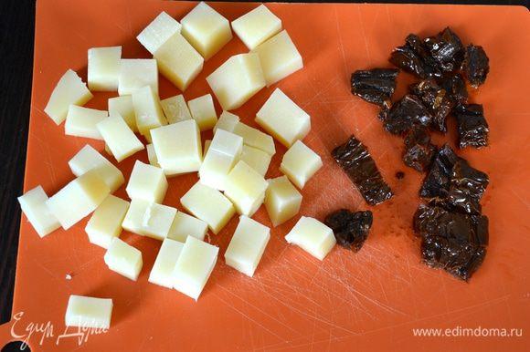 Тем временем подготовить сыр и вяленые томаты для начинки. Они должны быть комнатной температуры, поэтому в случае необходимости, достаньте их заранее из холодильника... Сыр нарезать небольшими кубиками, помидоры - небольшими кусочками (можно использовать вяленый помидорки-черри!).