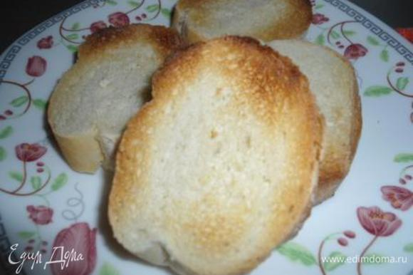 Багет порезать на кусочки и поджарить в тостере. Сбрызнуть оливковым маслом.