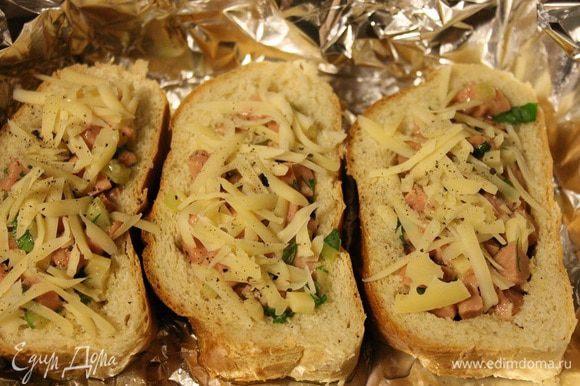 Оставшийся сыр натереть на крупной терке и посыпать им бутерброды. Выпекать в заранее разогретой до 190 градусов духовке, до тех пор, пока сыр сверху не расплавится.