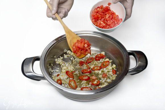 Помидоры полминуты бланшировать в кипящей воде, затем снять кожицу, мелко порезать, добавить к луку, чесноку и перцу чили. Тушить 10 минут.