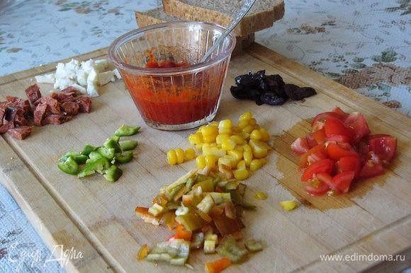 Подготовим необходимые продукты для пиццы: сыр, помидоры, перец, маслины или какие любите вы. Если хотите, подготовьте сосиски, ветчину или колбаски. Все мелко нарежем. У меня еще нашлась кукуруза. Перцовую пасту (можно заменить томатной) смешаем с оливковым маслом. Подготовим 3 кусочка черствого хлеба. Подойдет любой, какой у вас есть. Духовку включаем разогреваться до 180°С.