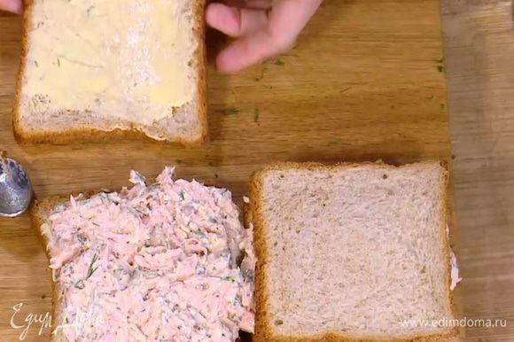 Куски хлеба смазать половиной сливочного масла, на два из них выложить рыбную начинку, равномерно распределить и накрыть оставшимся хлебом маслом вниз.