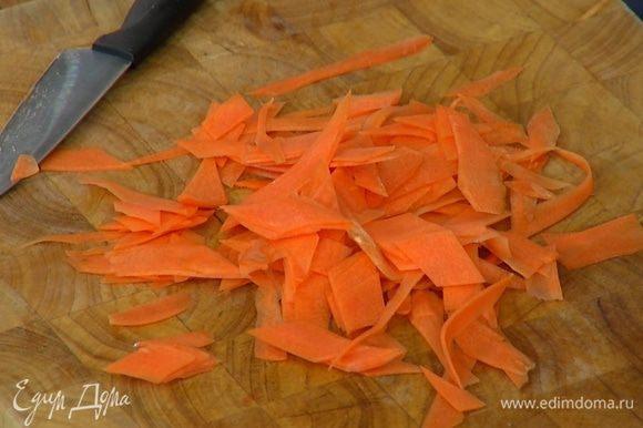 Морковь почистить и нарезать тонкими длинными полосками (можно воспользоваться овощечисткой), затем порезать полоски небольшими кусочками наискосок.