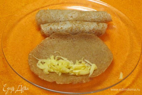 Выкладывать тертый сыр на каждый блинчик. Можно добавить мелко нарезанную ветчину. Свернуть в рулетики.