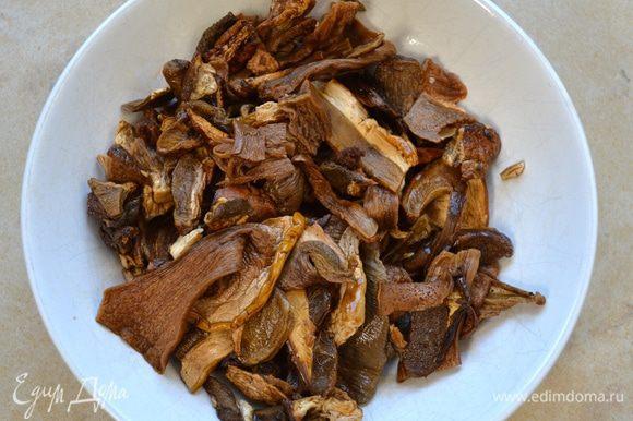 Замоченные грибы слейте и как следует отожмите. Добавьте их в сотейник к овощам. Помешивая, дайте грибам хорошо обжариться, до появления интенсивного запаха.