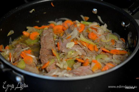 Затем добавим на эту же сковороду/жаровню порезанный сельдерей, морковь, лук готовить до мягкости овощей. Добавить чеснок 2 дольки мелко порубленный и тушить, помешивая, 2 минуты. Влить бульон, сухие грибы с жидкостью, вино. Вернуть мясо, перемешать. Тушить примерно 1 час. Разогреть духовку до 180°C.