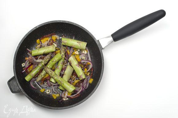 Когда лук станет золотистым, добавить спаржу и обжаривать все еще в течении 5 минут.