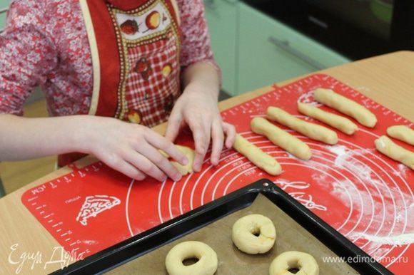Разделить тесто на кусочки, скатать небольшие колбаски, соединить концы в колечки. Разложить колечки на противень с бумагой для выпечки и отправить в разогретую духовку 180°C, на 10-15 минут.