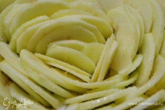 Смазать яблоки растопленным сливочным маслом и посыпать сахаром. Выпекать пирог в разогретой духовке при температур 180°С 40 минут.