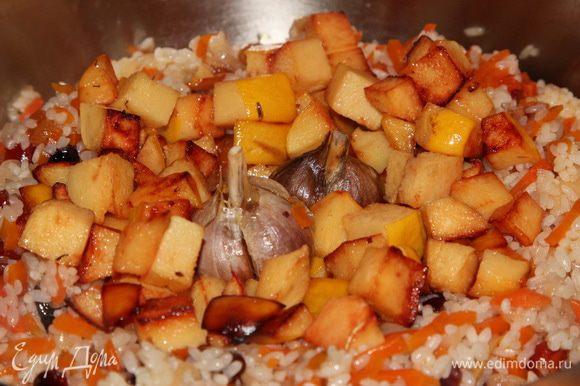 Добавляем температуру и перемешиваем все. Как только рис вберет в себя соус, снижаем температуру до минимума, выкладываем сверху поджаренную айву, чеснок и перец.