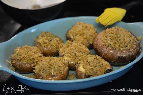 Заполнить шляпки грибов смесью. Сбрызнуть остатками масла. Поставить в горячую духовку на 25 минут.