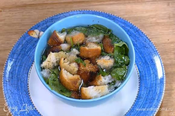 В глубокую тарелку выложить крутоны, кинзу и шпинат, залить все горячим бульоном, так чтобы шпинат немного привял, затем посолить, поперчить и добавить еще сухариков.