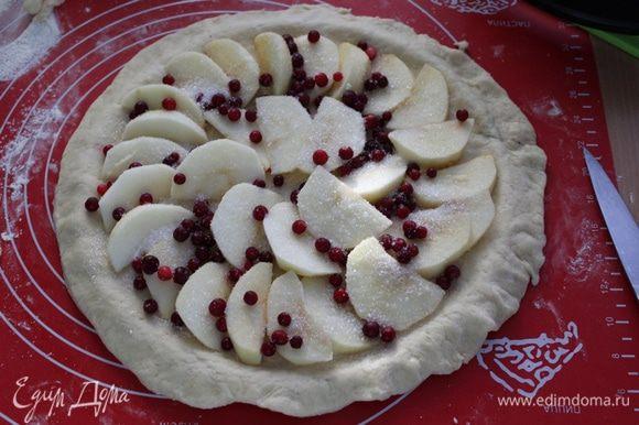 Поднявшееся тесто разделить на две неравные половинки, большую половинку раскатать и уложить в форму на 28, сделав бортики. Яблоки порезать дольками, выложить на тесто, посыпать ягодой и сахаром.
