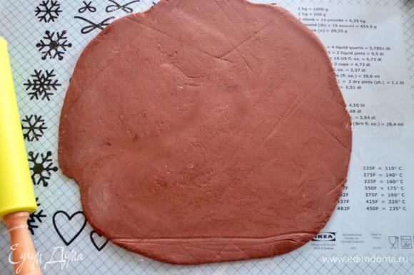 Подошедшее тесто выложить на рабочую поверхность и раскатать в круг диаметром примерно такого же размера, как и диск готового слоеного теста. Обильно смазать поверхность шоколадного теста растопленным сливочным маслом и присыпать сахаром.