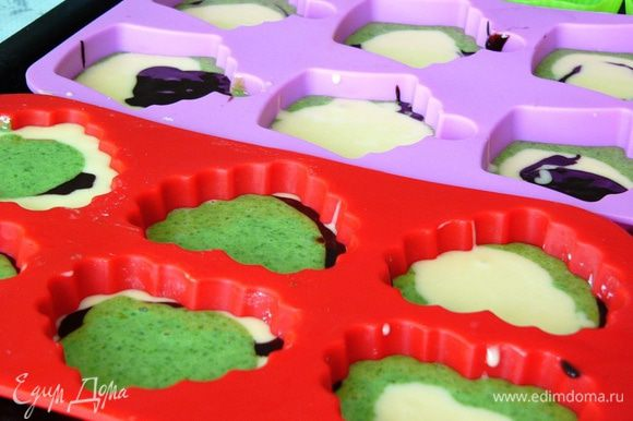 Формы для кексов или маффинов слегка промазываем маслом и произвольно выливаем в них разные виды теста, чередуя.