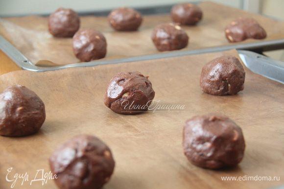 Убрать тесто в холодильник на 20-30 минут. Духовку разогреть до 180°C. Сформировать 12 шариков, выложить по 6 шариков на 2 стандартных противня. Между шариками должно быть значительное расстояние, поскольку при выпекании шарики трансформируются в лепёшки.