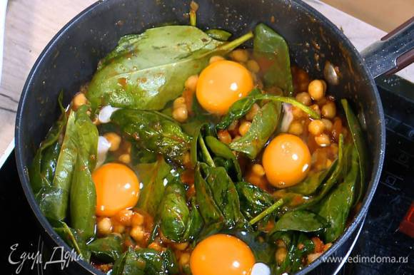 Яйца разбить на шпинат с нутом, накрыть сковороду крышкой и обжаривать все до готовности яиц.
