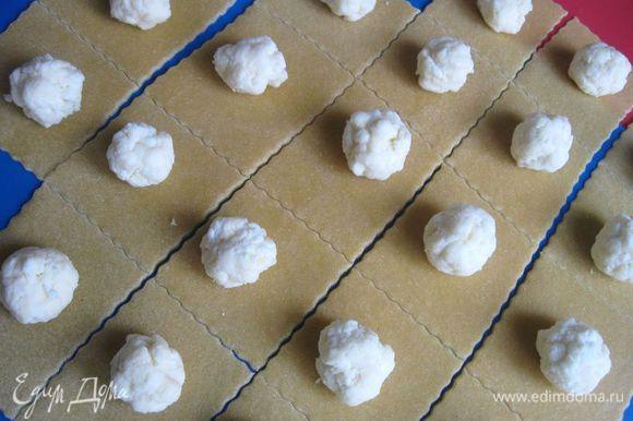 Нарезать тесто колесиком для пиццы на квадратики (размер стороны — 6 см или чуть больше). Такая форма позволяет экономить тесто.