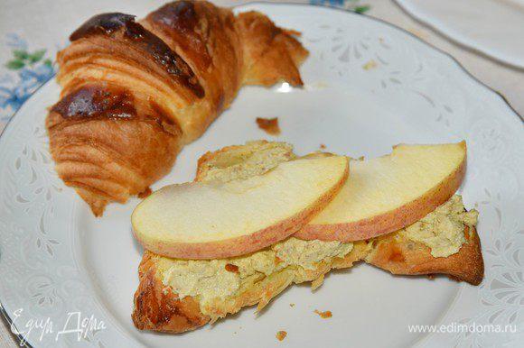 Добавить 1,5-2 столовых ложки оливкового масла и еще раз взбить. Соус готов. Его можно приготовить заранее и хранить в холодильнике в закрывающейся ёмкости в течение 3 дней. Яблоки нарезать на тонкие дольки. Круассаны разрезать вдоль на 2 части. На нижнюю часть щедро намазать соус, выложить дольки яблок, закрыть верхней частью.