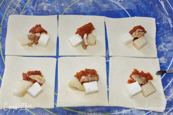 Тесто раскатать тонко, но следить, чтобы оно не порвалось. Нарезаем на квадраты и выкладываем по кусочку груши и сыра, половину чайной ложки томатов, половинку грецкого ореха. Начинку выкладываем вдоль диагонали, чтобы удобнее потом было складывать уголок. Края теста смазываем взбитым желтком.